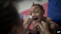 One-year-old Jose Wesley Campos, who was born with microcephaly, cries during a physical therapy session at the AACD rehabilitation center in Recife, Brazil, Sept. 28, 2016.