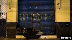 FILE - A homeless woman sleeps on a street on Christmas Eve in Sao Paulo, Brazil, Dec. 24, 2014.
