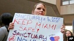 Manifestante tiene un cartel durante una manifestación en el centro de Miami. El alcalde del condado de Miami-Dade, Carlos Gimenez, emitió una orden asegurando a la administración Trump que Miami-Dade no está funcionando como una ciudad santuario para inmigrantes ilegales.