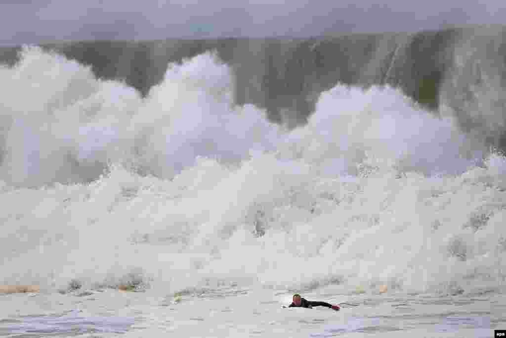 A surfer paddles back to shore when a huge wave crashes behind him at Narrabeen beach in Sydney's Northern Beaches, New South Wales, Australia.