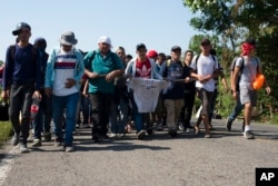Central American migrants, part of a caravan hoping to reach the U.S. border, walk on a road in Frontera Hidalgo, Mexico, April 12, 2019. The group pushed past police guarding the bridge and joined a group of about 2,000 migrants walking toward Tapachula.