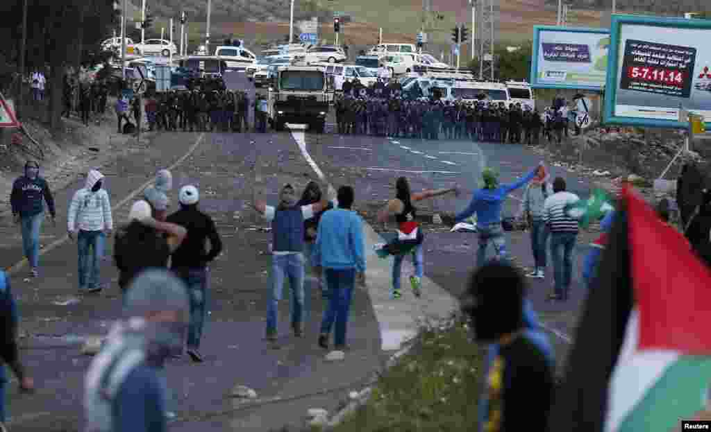 Israeli Arab youths clash with Israeli police at the entrance to the town of Kfar Kanna, northern Israel, Nov. 8, 2014.