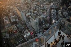 Turis mengambil gambar di tepi Shibuya Sky, Senin, 20 Januari 2020, di Tokyo. (Foto: AP)