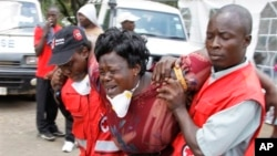 Red Cross staff console a woman after she viewed the body of a relative killed in Thursday's attack at a university in Garissa northeastern Kenya, at Chiromo funeral home, Nairobi, Kenya, Tuesday, April 7, 2015. Al-Shabab gunmen rampaged through a university in northeastern Kenya at dawn Thursday, killing scores of people in the group's deadliest attack in the East African country. (AP Photo/Khalil Senosi)
