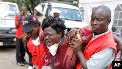 Elementos da Cruz Vermelha apoiam uma mulher após ela identificar o corpo de um familiar, vítima do ataque à universidade