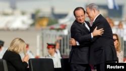 French President Francois Hollande (L) and Israeli Prime Minister Benjamin Netanyahu embrace during the official reception upon Hollande's arrival at Ben Gurion airport near Tel Aviv, Nov. 17, 2013.