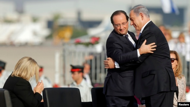 French President Francois Hollande (L) and Israeli Prime Minister Benjamin Netanyahu embrace during the official reception upon Hollande's arrival at Ben Gurion airport near Tel Aviv, Nov. 17, 2013.