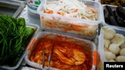 FILE - Korean style pickled cabbage, or Kimchi, and Chinese style pickled vegetables, or Pao Cai, are seen at a supermarket, in Beijing, China December 1, 2020. (REUTERS/Thomas Peter)