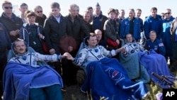 U.S. astronaut Thomas Marshburn, right, Russian cosmonaut Roman Romanenko, center, and Canadian astronaut Chris Hadfield, sit in chairs shortly after the landing of the Russian Soyuz TMA-07 space capsule, May 14, 2013.