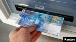 A couple of 100 franc bank notes are pulled from an ATM in Kreuzlingen, Switzerland.