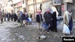 ພົນລະເຮືອນ ຖືເຄື່ອງຂອງໆພວກເຂົາເຈົ້າ ຂະນະທີ່ພາກັນ ຍ່າງໄປຫາຈຸດນັດພົບ ເພື່ອຍົກຍ້າຍອອກຈາກເມືອງ Homs ທີ່ຖືກທະຫານລັດຖະບານປິດລ້ອມ (7 ກຸມພາ 2014)