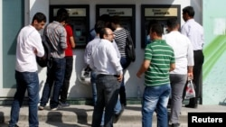People line in front of automated teller machines in Hatay, Turkey, May 17, 2013.