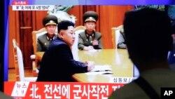Tin tức trên truyền hình tại một nhà ga xe lửa ở Hàn Quốc cho thấy lãnh tụ Bắc Triều Tiên Kim Jong Un họp với các tướng lãnh Bắc Triều Tiên, ngày 21/8/2015.