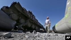 A man looks at a destroyed Ukrainian army tank near the village of Lebedynske, on the highway joining Mariupol and Novoazovsk, Ukraine, Sept. 6, 2014.