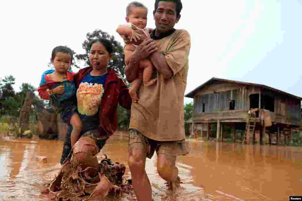 라오스 아타프 주에서 세피안-세남노이댐이 붕괴된 후 홍수로 집을 잃은 부부가 어린 아이들을 안은 채 대피하고 있다. 지난 23일 수력발전소 보조댐에서 많은 양의 물이 인근 6개 마을을 덮치면서 지금까지 20여 명의 사망자가 발생하고 130명이 넘는 실종자가 나왔다.