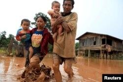 26일 라오스 아타프 주에서 세피안-세남노이댐이 붕괴된 후 홍수로 집을 잃은 부부가 어린 아이들을 안은 채 대피하고 있다. 지난 23일 수력발전소 보조댐에서 많은 양의 물이 인근 6개 마을을 덮치면서 지금까지 20여 명의 사망자가 발생하고 130명이 넘는 실종자가 나왔다.