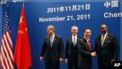 中國副總理王歧山(右二)和美國貿易代表柯克在第22屆中美商貿聯委會會議上握手﹐左二為美國商務部長布賴森。
