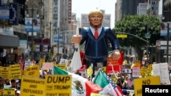 FILE - People march with an inflatable effigy of Republican presidential candidate Donald Trump during an immigrant rights May Day rally in Los Angeles, California, May 1, 2016.