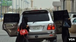 Dua perempuan Saudi keluar dari sebuah mobil di Riyadh (17/6).