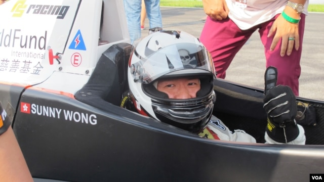 Sunny Wong in the PS Racing car, with ChildFund International decals behind, Sept. 15, 2013.