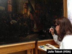 "Marta Brassfield, one of the Senior Painting Conservators with Olin Conservation, Inc., uses a fine brush to inpaint damaged areas of ""Borne by Loving Hands,"" a painting by German artist Carl Bersch that captures the aftermath of President Abraham Lincoln's assassination."