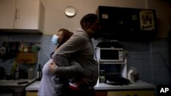 Andrea Cortes demonstrates how she embraces her husband amid the new coronavirus pandemic, while standing in their kitchen in Buenos Aires, Argentina, Monday, July 13, 2020. (AP Photo/Natacha Pisarenko)