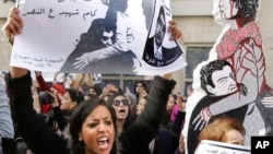"An Egyptian protester chants anti-Interior Ministry slogans as she holds a poster of Shaimaa el-Sabagh, an activist who was shot dead at a peaceful protest last Saturday, with Arabic that reads, ""How many martyrs remaining for victory."""