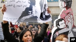 """An Egyptian protester chants anti interior ministry slogans as she holds a poster of Shaimaa el-Sabagh, an activist who was shot dead at a small peaceful protest last Saturday, with Arabic that reads, """" how many martyrs remaining for victory,"""" during a wo"""