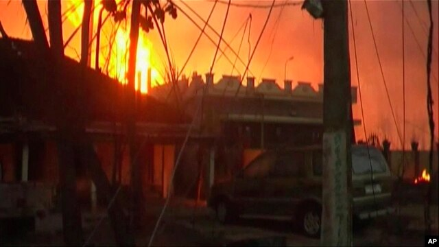 In this image taken from video, flames rise in the background of houses after a state-owned gas pipeline exploded in Nagaram village, in the southern Indian state of Andhra Pradesh  Friday, June 27, 2014.