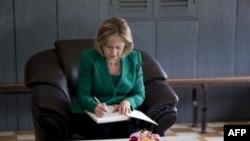 """Хиллари Клинтон оставляет запись в книге посетителей музея памяти жертв """"красных кхмеров"""" в Камбодже."""