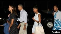 Presiden AS Barack Obama, Ibu Negara Michelle Obama (kanan), Malia (kiri) dan Sasha tiba di Honolulu, Hawaii untuk liburan Natal dan Tahun Baru (19/12).