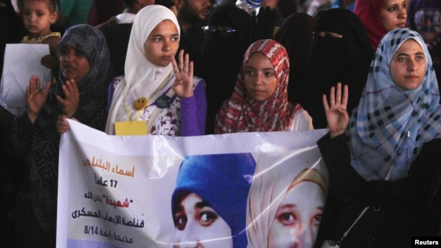 "Supporters of ousted Egyptian President Mohamed Morsi rally against the military and interior ministry, as they show the ""Rabaa"" gesture, a sign to condemn police killing of hundreds of protesters."