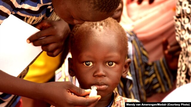 FILE - A child takes a dose of oral cholera vaccine at UNMISS Tomping camp in Juba.