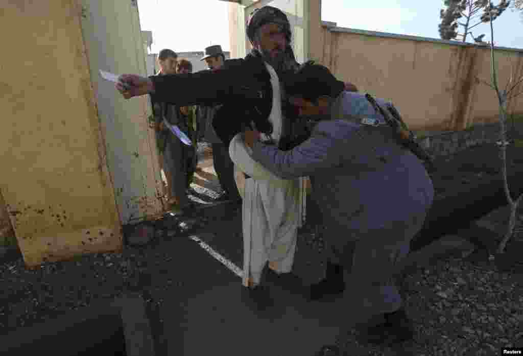 An Afghan policeman searches men before they enter a polling station in Adraskan district, Herat province.