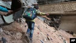 A child navigates rubble and barbed wire in Aleppo, Syria, Feb. 11, 2016.