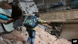 ក្មេងម្នាក់កំពុងដើរក្បែរកម្ទេចអាគារនិងបន្លាលួសនៅក្នុងទីក្រុង Aleppo ប្រទេសស៊ីរី កាលពីថ្ងៃទី១១ ខែ កុម្ភៈ ឆ្នាំ២០១៦។