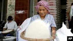 A Cambodian vendor cleans rice at her shop in a roadside market in Phnom Penh, Cambodia. (AP Photo/Heng Sinith)