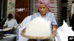 A Cambodian vendor cleans rice at her shop in a roadside market in Phnom Penh, file photo.