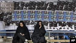 3月1号,两名伊朗妇女在等车,公车站贴满了议会选举的海报。