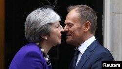 PM Inggris Theresa May (kiri) menyambut kunjungan Presiden Dewan Eropa, Donald Tusk di luar kantornya Downing Street 10, di London, Inggris hari Kamis (1/3).