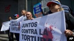 """Venezuela: Activistas da oposição com estandarte onde se lê """"Juntos contra a tortura"""""""