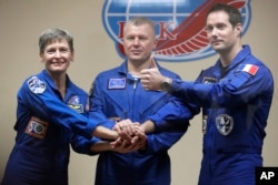 French astronaut Thomas Pesquet (right) Russian cosmonaut Oleg Novitsky and U.S. astronaut Peggy Whitson, members of the main crew to the International Space Station, pose after a news conference in Russian leased Baikonur cosmodrome, Kazakhstan, Nov. 16, 2016.
