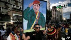 A government supporter carries a painting of Venezuela's late President Hugo Chavez in Caracas, Venezuela, Tuesday, Jan. 5, 2016, to protest the swearing-in of opposition lawmakers. (AP Photo/Alejandro Cegarra)