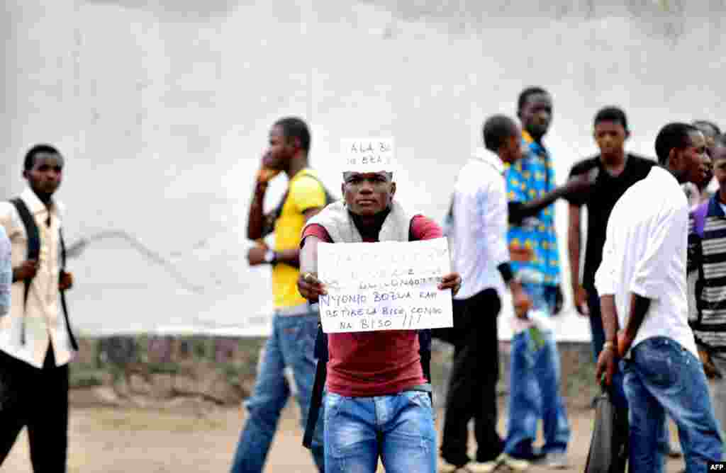 "A student from the Architecture and Urbanism institute holds a sign protesting against civil unrest outside of their university in Kinshasa. The sign reads: ""Too much is too much. What do you want with the Congo."""