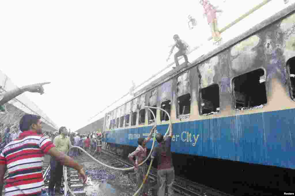 People help to control a fire set on a train during protests at Kamlapur Railway Station in Dhaka, Bangladesh, March 4, 2013.