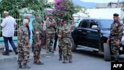 """Des soldats de la base des forces armées des Comores attendent à l'extérieur de la """"Médina"""" à Mutsamudu, à Anjouan, Comores, 19 octobre 2018."""