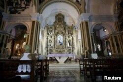 A woman sits in a Roman Catholic church in Havana, Sept. 17, 2015.