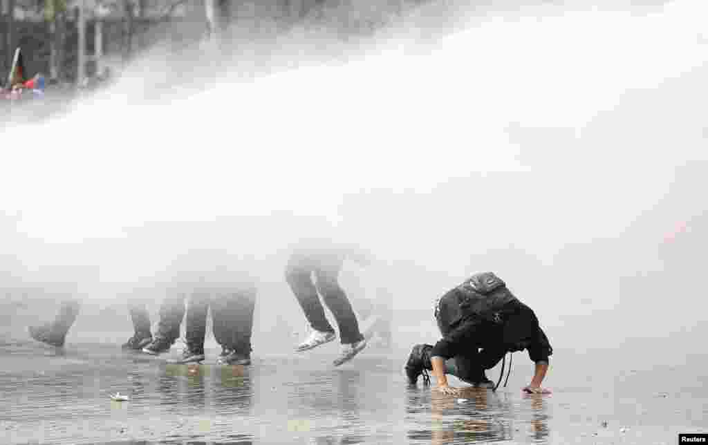 Student protesters are hit by a jet of water released from a riot police water cannon during a demonstration against the government to demand changes in the public state education system in Santiago, Chile, Sept. 5, 2013.