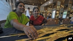 A woman browses gold waist belts at a jewelery shop during the Akshaya Tritiya festival in the southern Indian city of Hyderabad May 6, 2011.