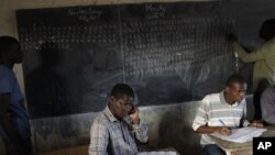 Election workers tally votes on a blackboard during vote counting at a polling station in the Medina neighborhood of Dakar, Senegal Sunday, March 25, 2012.
